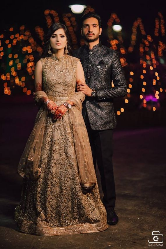 Photo of bride and groom in contrasting engagement outfits