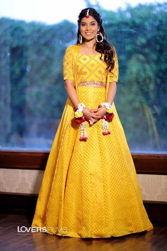 Photo of mustard yellow lehenga with floral jewellery for mehendi or haldi