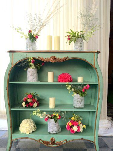 Photo of mint colored wooden chest with candles and flower arrangement