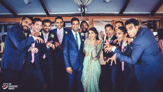 Photo of Bride and Groom Posing with Matching Groomsmen