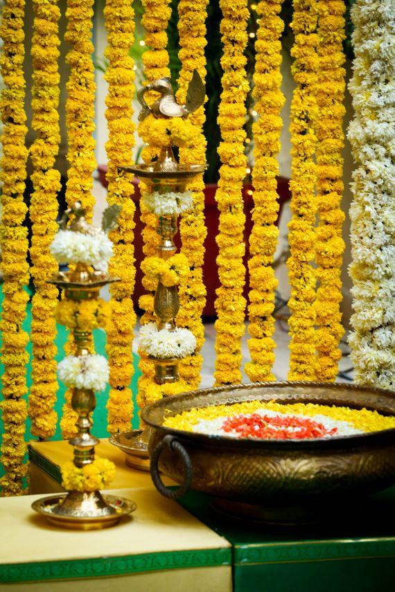 Photo of south Indian telegu wedding decor traditional mehendi decor with genda flower strings