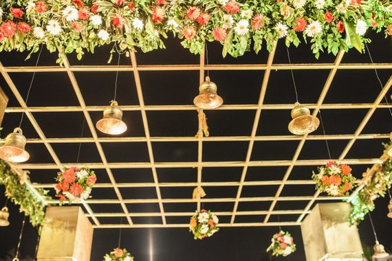 Photo of Gold Temple Theme Mandap with Bells and Flowers