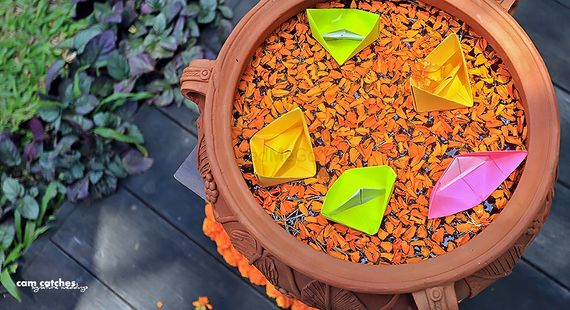 Photo of Earthen pot with floating petals and paper boats