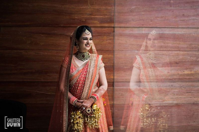 Photo of Bride in orange lehenga and kaleere