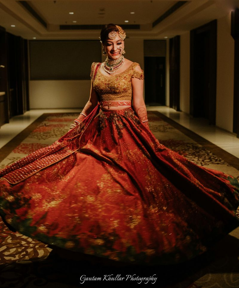Photo of Gold and red lehenga twirling bride